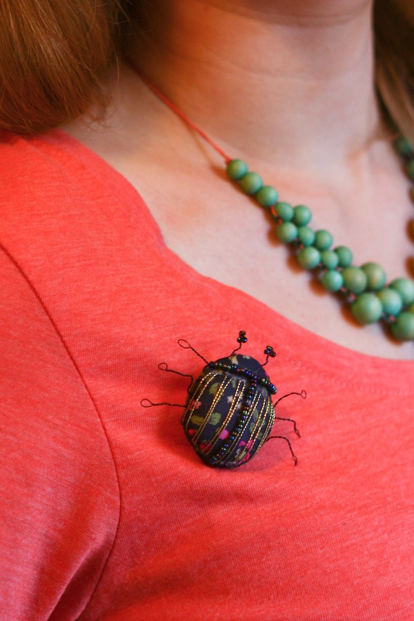 Брошь жук из бисера приколота к груди
