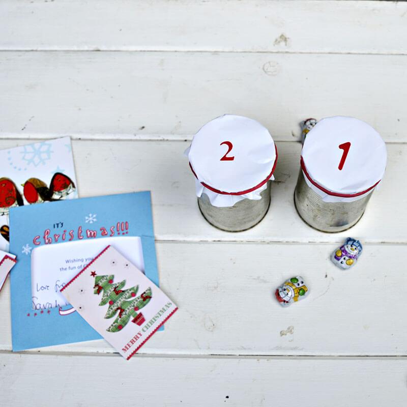 Как сделать анвент календарь из жестяных банок - накройте банки бумажными дисками и закрепите их резинками